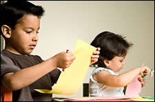 Children cutting with scissors and drawing